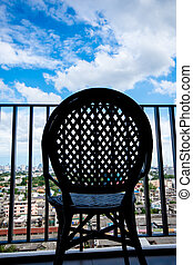 The silhouette of chair at balcony with blue sky in background