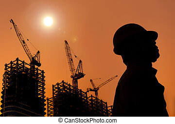 The Silhouette of Construction workers with sunset