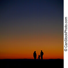 The silhouette of family watching the sunrise