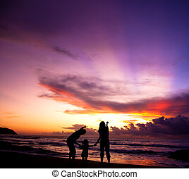 The silhouette of family watching the sunrise on the beach
