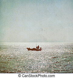 The silhouette of fisherman with boat in the sea vintage background