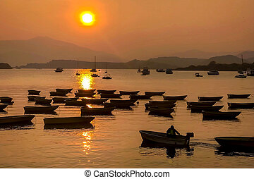 silhouette of fishing boat on lake with sun and mountain at sunset