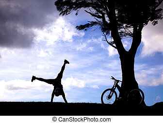 The Silhouette of mountain biker with handstand on the hill