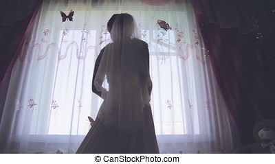 the silhouette of the bride against the window