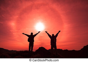 The Silhouette of two man with success gesture