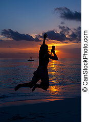 the silhouette of woman, who jumps on a beach