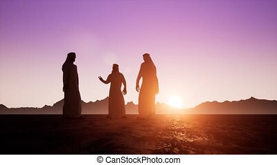 The silhouettes of three Arabs in dishdasha are talking to each other. Beautiful dawn