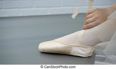 The silk pointe is tied up on the leg of ballerina sitting...