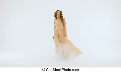 The singer in a long beautiful dress sings on the background of a white wall. slow motion