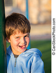 Beautiful six year old boy laughs and hides. Playground in winter sunny day