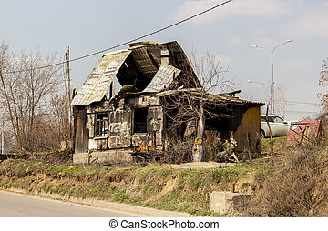 The skeleton of a burnt wooden house, a residential building after a fire, without treatment