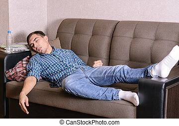 The sleeping young man on the couch in the room, tired after work, drunk after a party. Fell asleep anyhow.