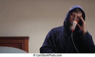 The sleepy patient man in oxygen mask in hood dark blue bathrobe portrait interior looking at camera