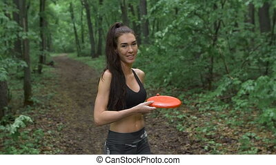 The slender fitness girl playing with someone in a frisbee. She throws the plate to his partner.