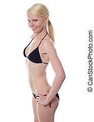 The slim suntanned girl in bikini, isolated on white