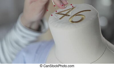 The slow motion video of designer of clothes works with a dummy in sewing agency, the size is 46, hands of the master in sewing with blue fabric, sewing needles with a red tip, 120 fps