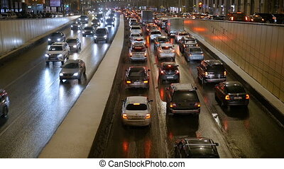 The slow movement of vehicles on city streets. In evening time.
