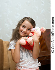 The small friend - portrait of a small girl with a pig-toy