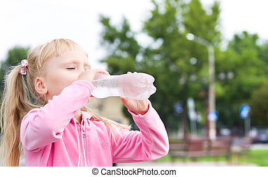 The small girl is drinking water
