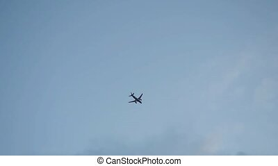 The small silhouette plane flying across the blue sky and...