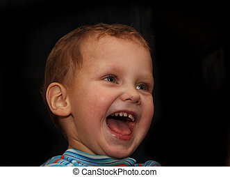 The smiling boy. A portrait on a black background