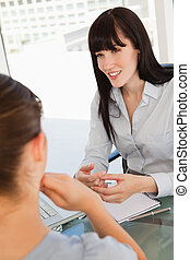 The smiling business lady chats with a fellow employee