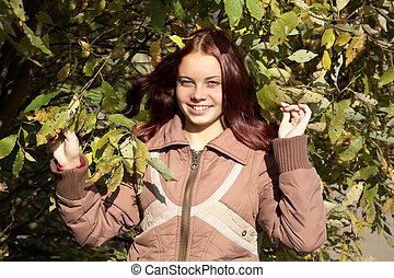 The smiling girl against a tree