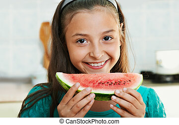 The smiling girl is eating the watermelon
