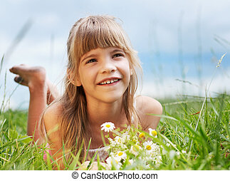 The smiling girl is lying in the meadow