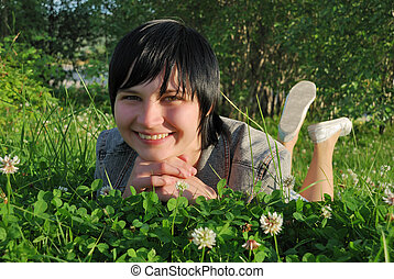 The smiling girl, lying in a grass.
