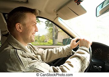 The smiling young man drives the car