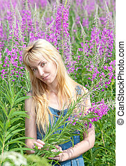 The smiling young woman with bunch of willowherb flower in the field
