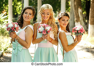 The smilling bridesmaids with bouquet