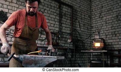 The smith knocks on a hot rod with a hammer - Blacksmith...
