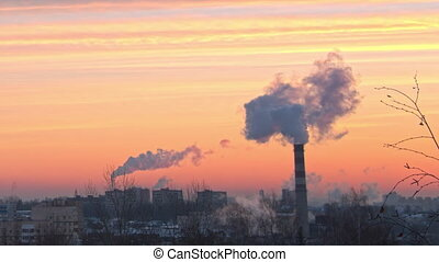 the smoke from the chimney of the plant against the dawn in the city