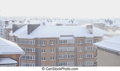 The smoke from the chimneys of a five-story residential home in winter