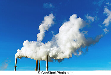 the smoking chimneys of a factory against a blue sky. white smoke rising from chimneys at