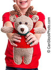 The soft toy of deer in the happy boy's hands front view. Concept: christmas or Happy New Year holiday