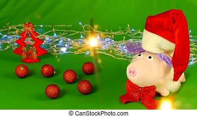 The soft toy pig in a Santa Claus hat stands on a hromakey...