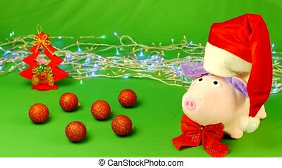 The soft toy pig in a Santa Claus hat stands on a hromakey,...