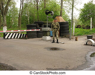 The soldier on control check point. Control of the mode of the admission.