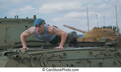 The soldier pushed on the tank. Training on a military base. A man in a blue beret and vest