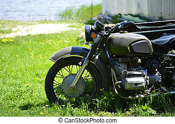 The Soviet Dnepr motorcycle on the green grass of the front part close up against a sandy shore by the lake.