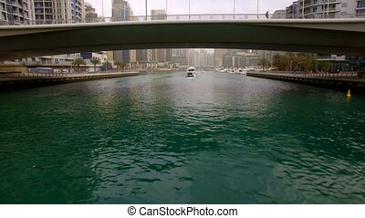 the span of the camera under the bridge following behind the floating boat in Dubai Marina. Bottom visible green water and the sides are skyscrapers