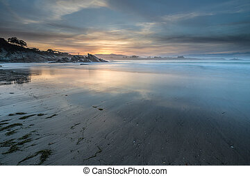 the spectacular reflections of the sunset on the beach