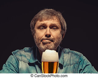 Enjoying his favorite beer. The front view of handsome spellbound man in denim shirt with glass of beer, sitting at the wooden table. Concept of desire and love for beer