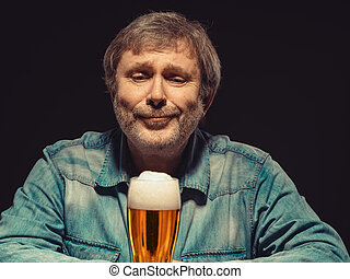 Enjoying his favorite beer. The front view of handsome spellbound man in denim shirt with glass of beer, sitting at the wooden table. Concept of desire and love for beer and tender emotion