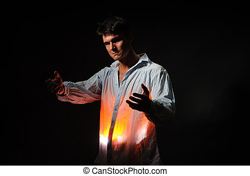 The sexy man has his hands out in front of him with a glowing light under his shirt.