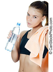 The sports girl with a towel and a water bottle