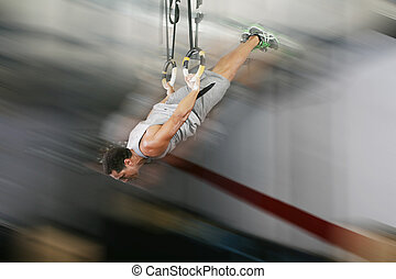 The sportsman the guy, carries out difficult exercise, sports gymnastics, on gym